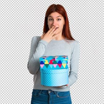 선물을 받았기 때문에 놀란 젊은 빨강 머리 소녀