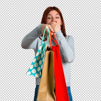 Young redhead girl surprised and holding a lot of shopping bags