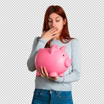 Young redhead girl surprised while holding a big piggybank