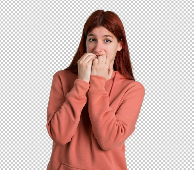 Young redhead girl with pink sweatshirt is a little bit nervous and scared putting hands to mouth