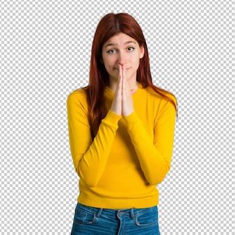 Молодая рыжая девушка с желтым свитером держит ладонь вместе. человек просит чего-то