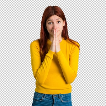 Young redhead girl with yellow sweater keeps palm together. person asks for something