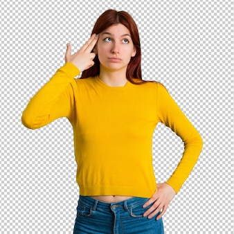 Young redhead girl with yellow sweater with problems and with unhappy expression