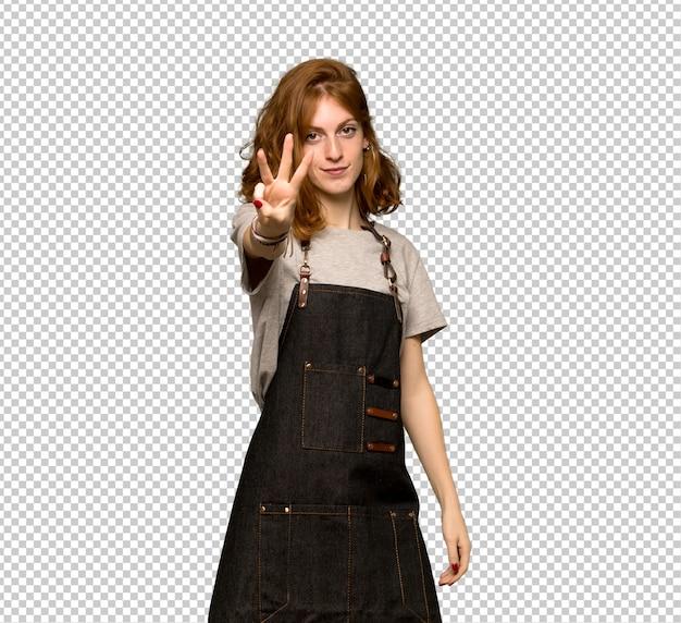 Рыжая молодая женщина с фартук счастливым и считая три с пальцами