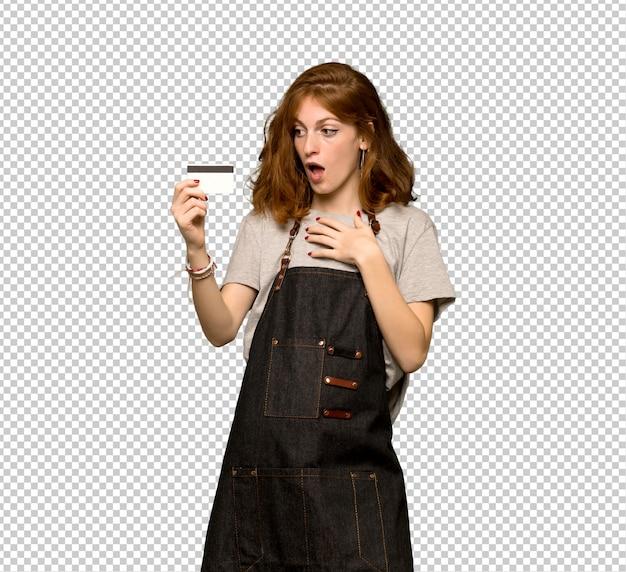 Молодая рыжая женщина с фартуком держит кредитную карту и удивлена