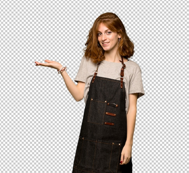 Young redhead woman with apron holding copyspace imaginary on the palm to insert an ad