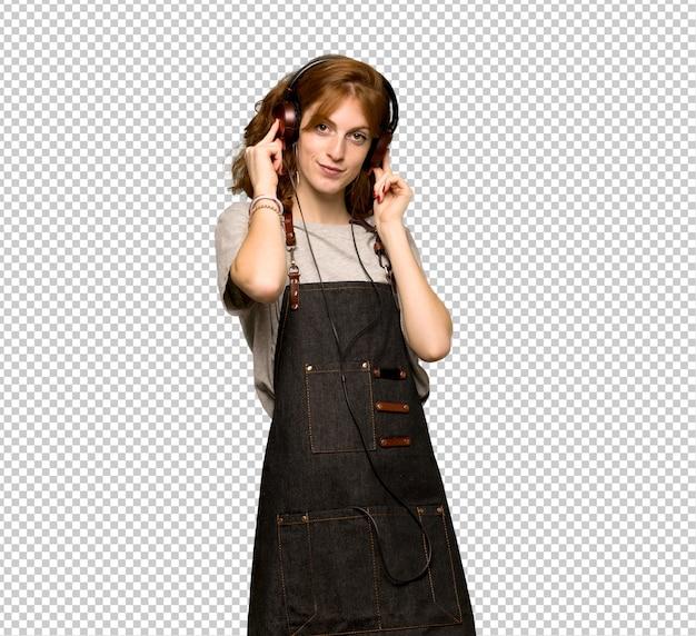 Рыжая молодая женщина с фартуком, слушая музыку в наушниках