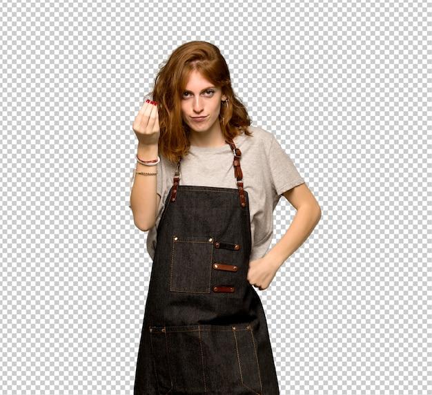 Молодая рыжая женщина с фартуком делает итальянский жест