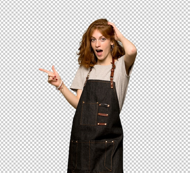 Young redhead woman with apron pointing finger to the side and presenting a product