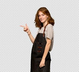 横位置で側に指を指しているエプロンを持つ若い赤毛の女性