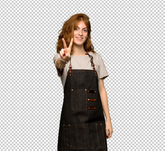 Рыжая молодая женщина с фартук улыбается и показывает знак победы