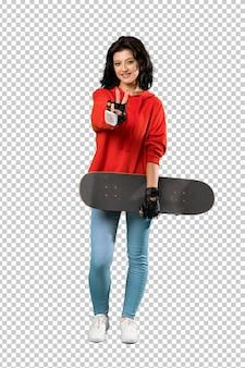 Молодая фигуристка улыбается и показывает знак победы