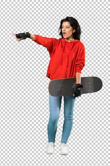 Young skater woman surprised and pointing finger to the side