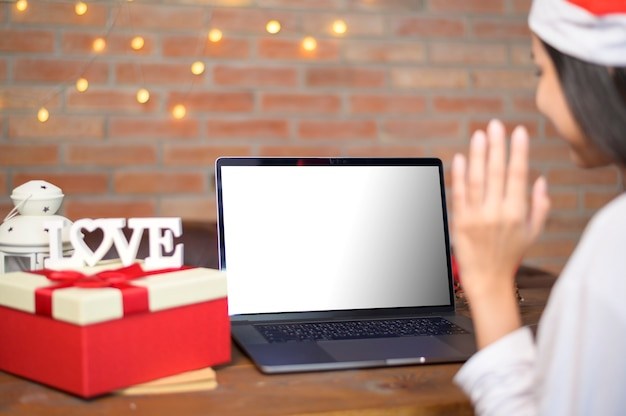 Young smiling woman wearing red santa claus hat making video call on laptop mockup