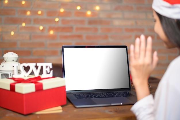 Молодая улыбающаяся женщина в красной шляпе санта-клауса делает видеозвонок на макете ноутбука