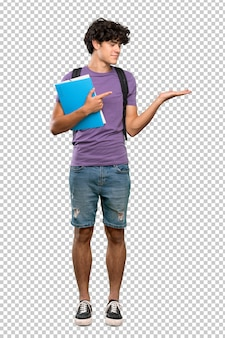Young student man holding copyspace imaginary on the palm to insert an ad