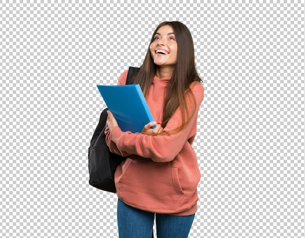 Young student woman holding notebooks looking up while smiling