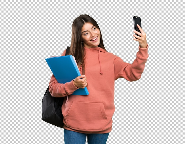 Young student woman holding notebooks making a selfie