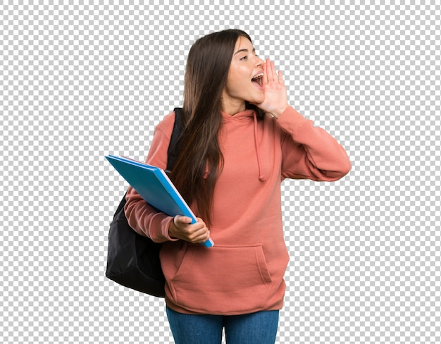 Young student woman holding notebooks shouting with mouth wide open to the lateral