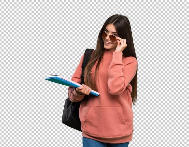Молодая женщина студента держа тетради с стеклами и счастливое