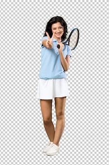 Молодая теннисистка улыбается и показывает знак победы