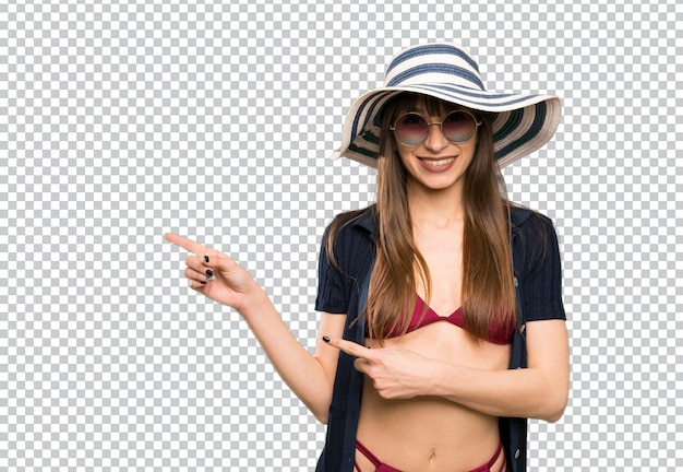 Young woman in bikini pointing finger to the side