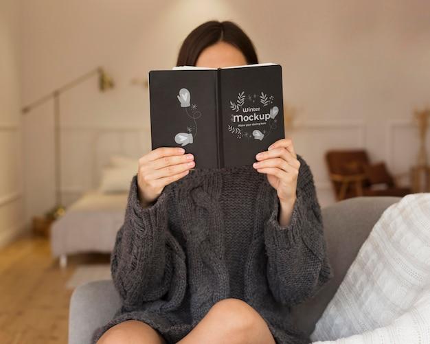 本のモックアップを保持している若い女性