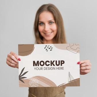 モックアップ紙を保持している若い女性