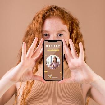 スマートフォンのモックアップを保持している若い女性
