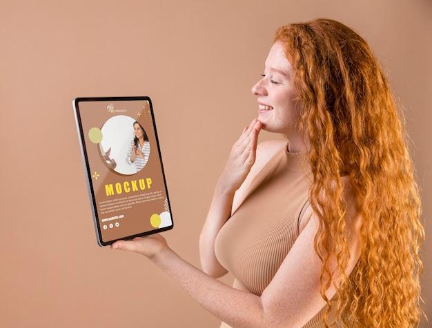 태블릿 모형을 들고 젊은 여자