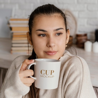 Young woman holding a mock-up cup
