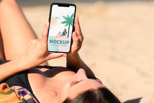 Giovane donna che tiene uno smartphone mock-up