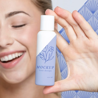 Young woman holding a skincare product mock-up