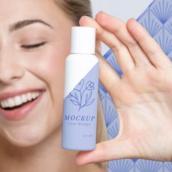 Giovane donna che tiene un modello di prodotto per la cura della pelle