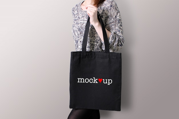 Young woman is holding a black tote bag, mockup.