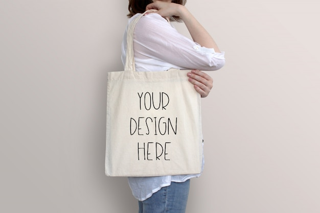 Young woman is holding tote bag, mockup
