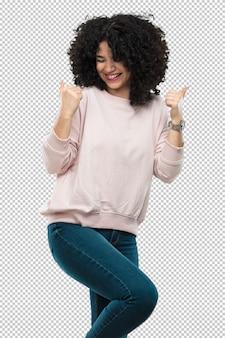 Молодая женщина смеется и делает жест победителя