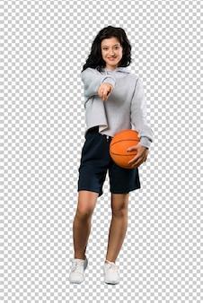 Молодая женщина, играющая в баскетбол, уверенно показывает пальцем на тебя