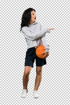 Young woman playing basketball surprised and pointing side