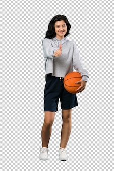 Young woman playing basketball with thumbs up because something good has happened