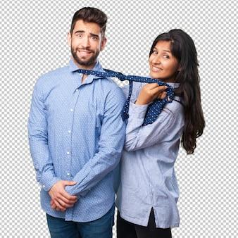 Молодая женщина вытягивает мужчину из галстука