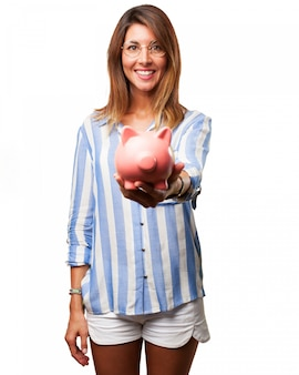Young woman in shorts showing her piggy bank