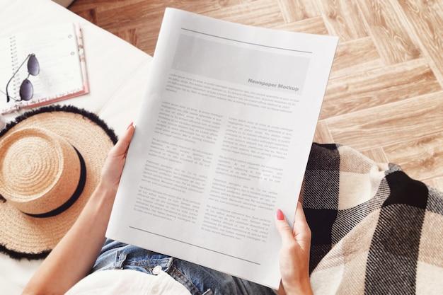リビングルームに座っていると新聞のモックアップを読む若い女性