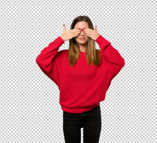 Молодая женщина с красным свитер, охватывающих глаза руками. удивлен, увидев, что впереди