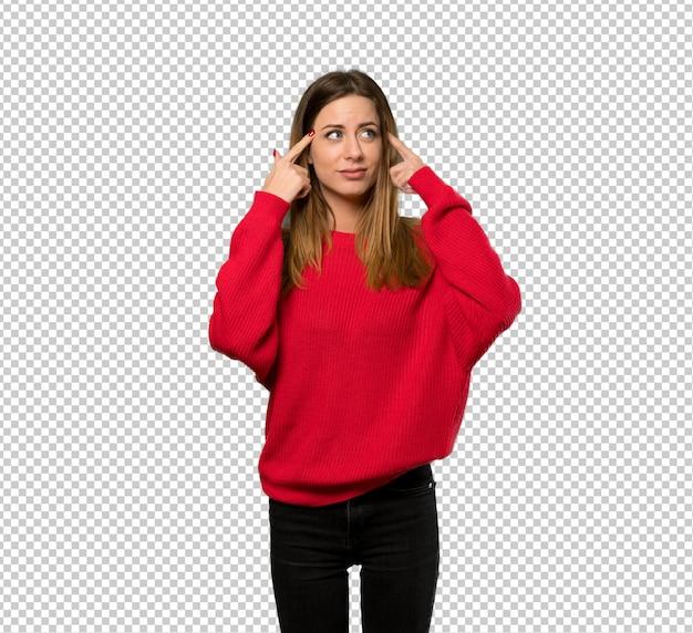 疑問や考えを持つ赤いセーターを持つ若い女