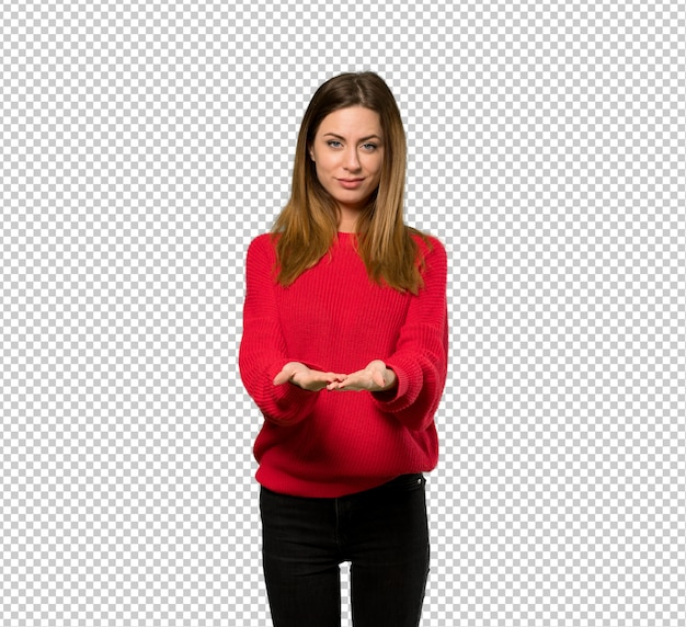 Young woman with red sweater holding copyspace imaginary on the palm to insert an ad