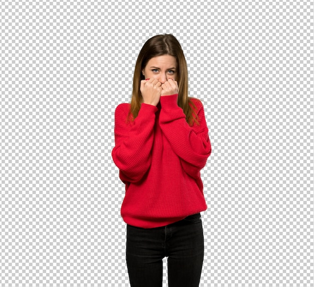 Young woman with red sweater nervous and scared putting hands to mouth