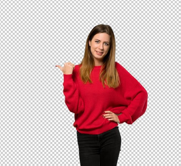Молодая женщина с красным свитером, указывая на сторону, чтобы представить продукт