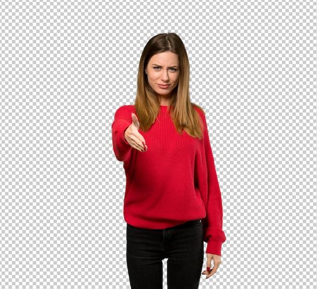 Молодая женщина с красным свитером рукопожатие для закрытия хорошей сделки