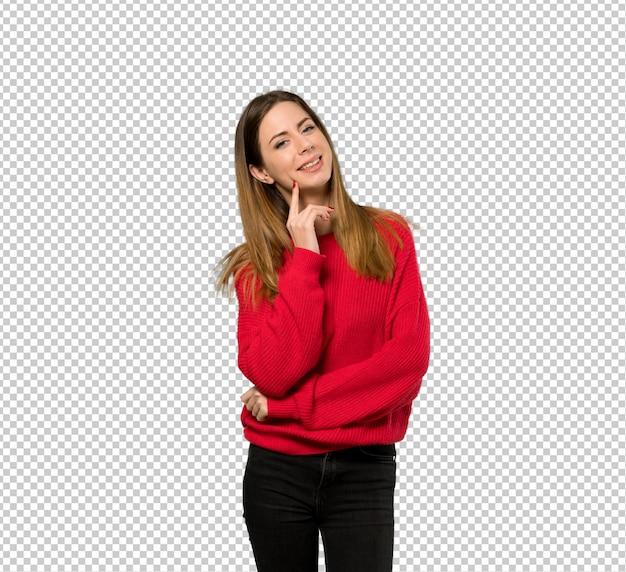 Молодая женщина с красным свитером думая идея пока смотрящ вверх